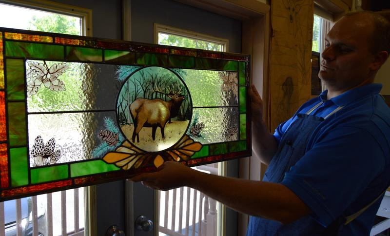Dirk Thompson, Jr. holding one of the wildlife themed stained glass pieces produced by the shop.
