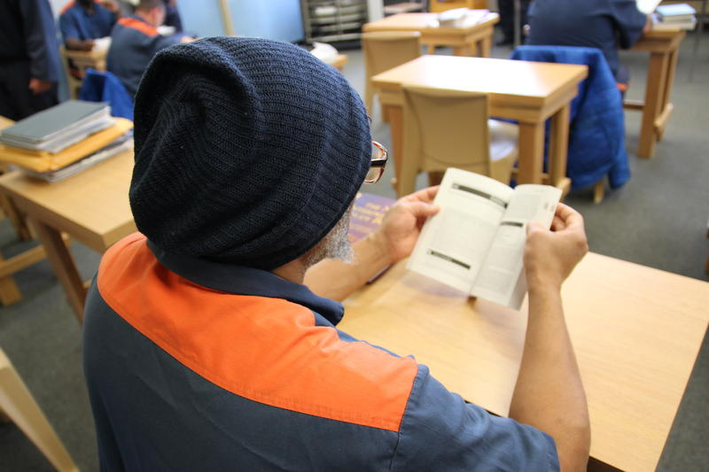 A student inmate reads in class