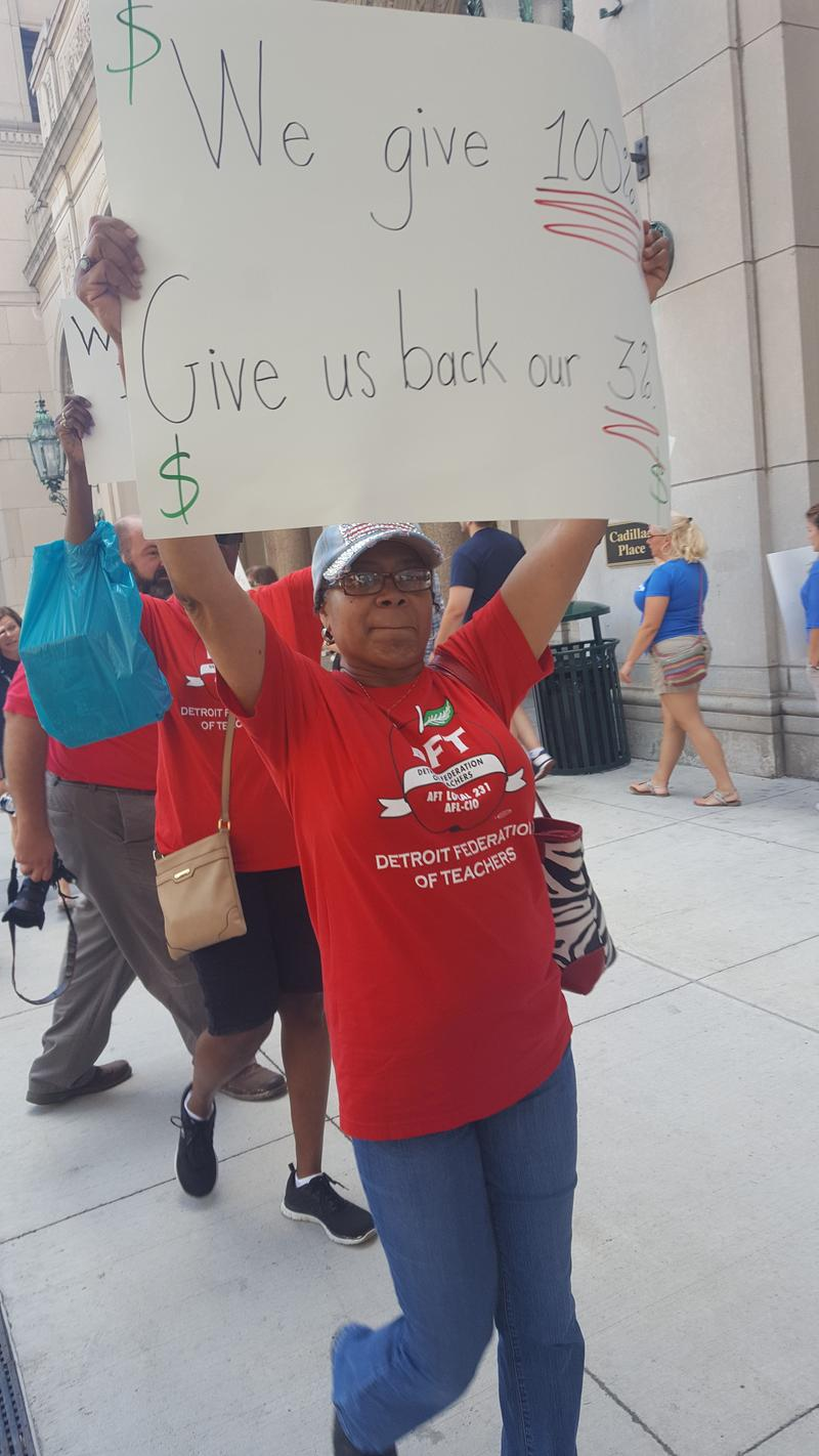 A member of the Detroit Federation of Teachers protests Governor Snyder's latest appeal of a case involving teacher's pay.