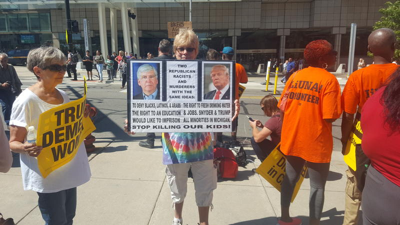 Protestors stand outside of Cobo Hall in Detroit to show their dislike of Donald Trump.