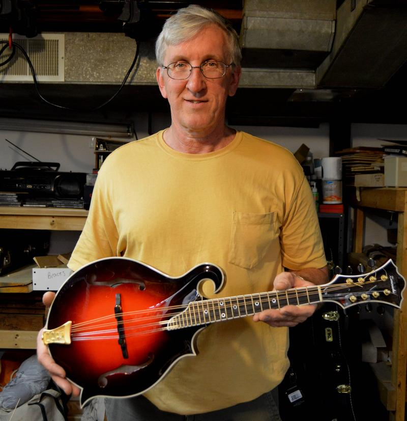 Gary Zimnicki holding a mandolin he built.