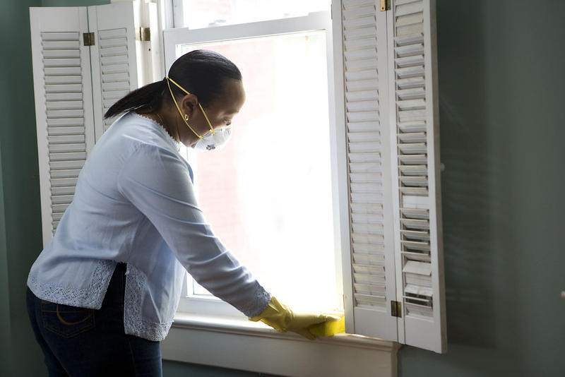 Woman cleaning sills with damp cloth to remove lead dust
