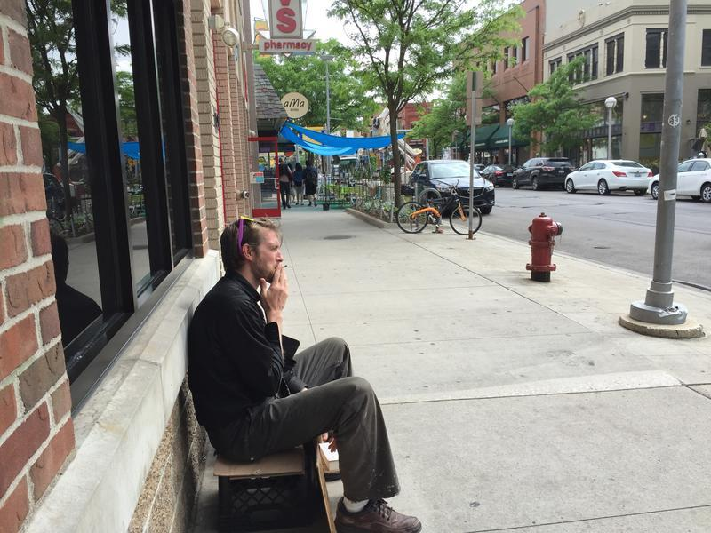A man panhandles on State Street in Ann Arbor.
