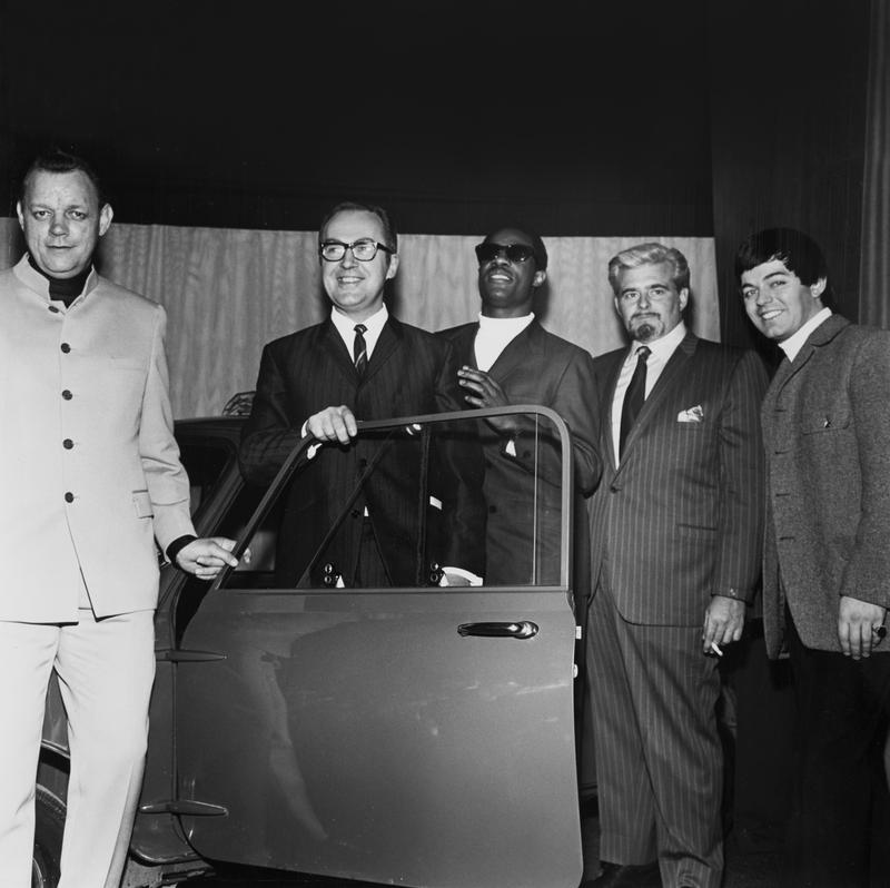 "Stevie Wonder presents a ""Motown Mini"" to a British competition winner in London, 1969, alongside the company's Phil Jones and Barney Ales and, at right, DJ Tony Blackburn."