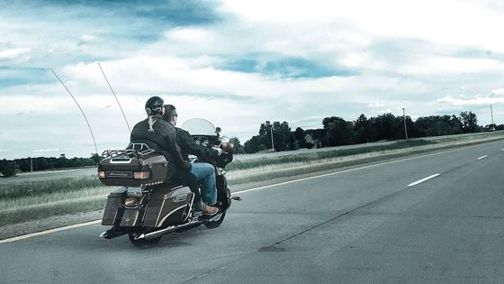 A motorcyle rider with no helmet and a passenger with a helmet.