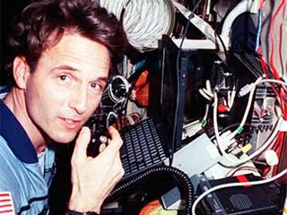 Jerry Linenger with ham radio equipment in the Russian Mir Space Station Base Block module.