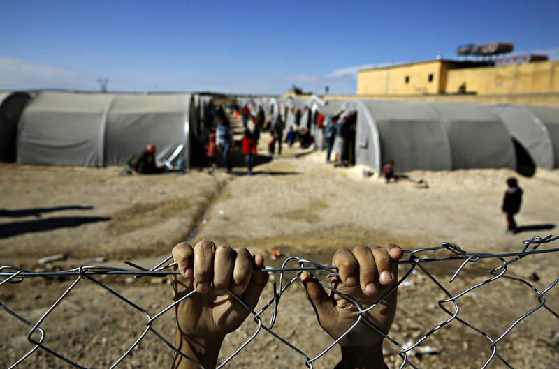 child holds onto a fence that surrounds a refugee camp