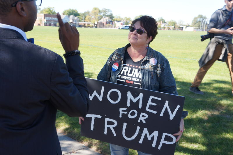 woman holding sign that says women for trump