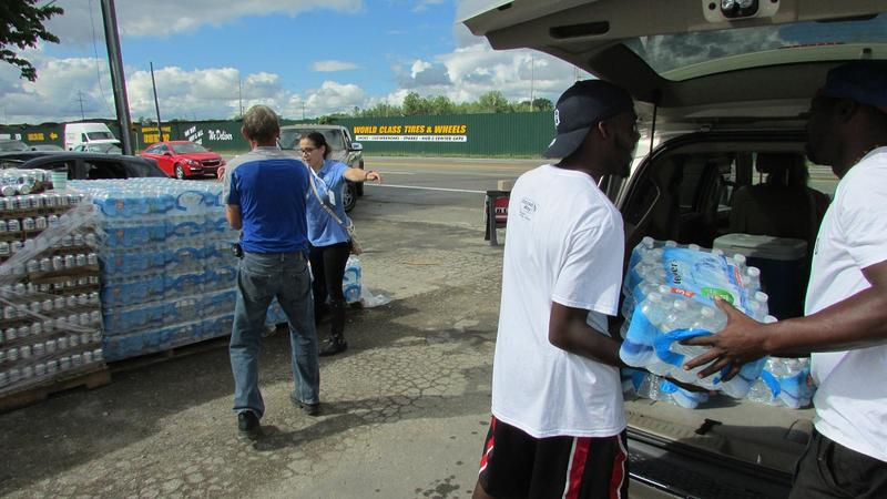 Flint residents pick up bottled water at one of 9 distribution centers