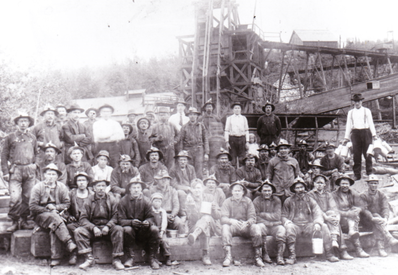 Barnes-Hecker men in the years before 1926. Children shown would bring their fathers' lunch pails to the mine during the noon hour. Front row fourth from left with boy seated next to him is Mine Captain William Tippett, who also perished in the disaster.