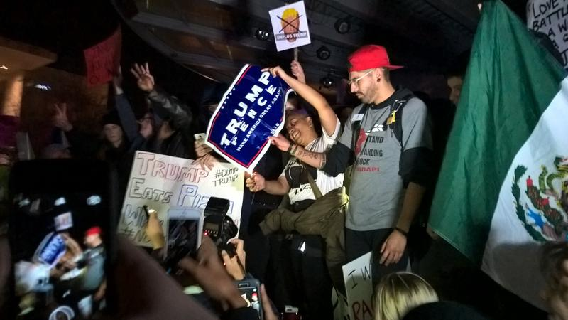 Protestors try to light a Trump campaign sign on fire. They ripped it up instead, at the crowd's urging.