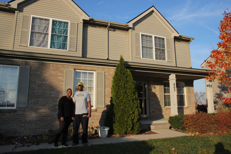 Dana and Charles Banks in front of their Flint home, shortly before they sold it..