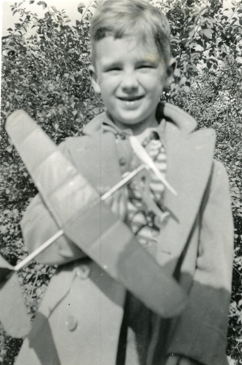 Roger, age 5, missing his front teeth and holding a model plane built by his father.