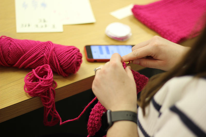 A student works on knitting a pussyhat, an initiative of the Pussyhat Project, which seeks to provide Women's March participants and supports a visual statement to be seen and heard.