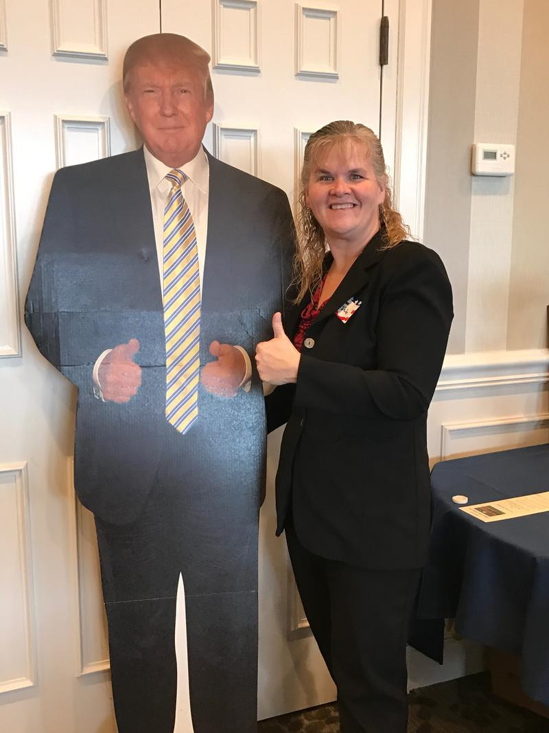 Renee White with a cardboard cutout of Trump