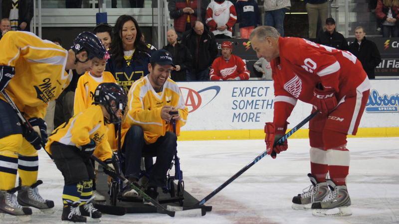 Former Michigan hockey player Scott Matzka drops the puck at center ice to start the alumni game.