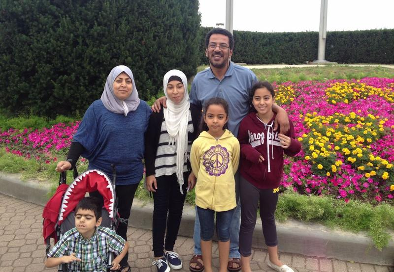 Yousef Ajin stands with his family. His wife and kids are U.S. citizens. He has been working toward citizenship, but now faces the possibility of being deported.