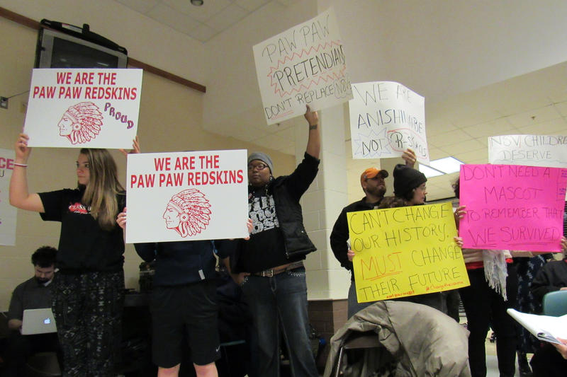 Competing signs at the Paw Paw school board meeting Wednesday night.