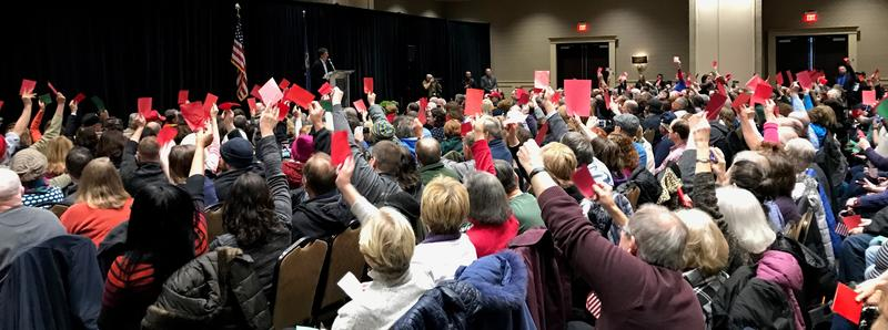 People who attended the town hall with Rep. Dave Trott (R-11th) used green and red colored cards to show approval or disagreement.
