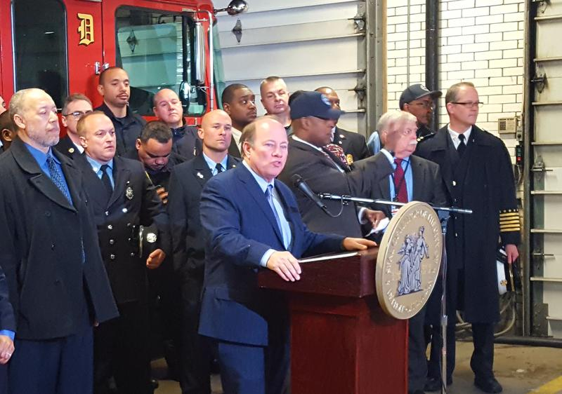 Detroit Mayor Mike Duggan speaking to media, surrounded by Detroit firefighters.