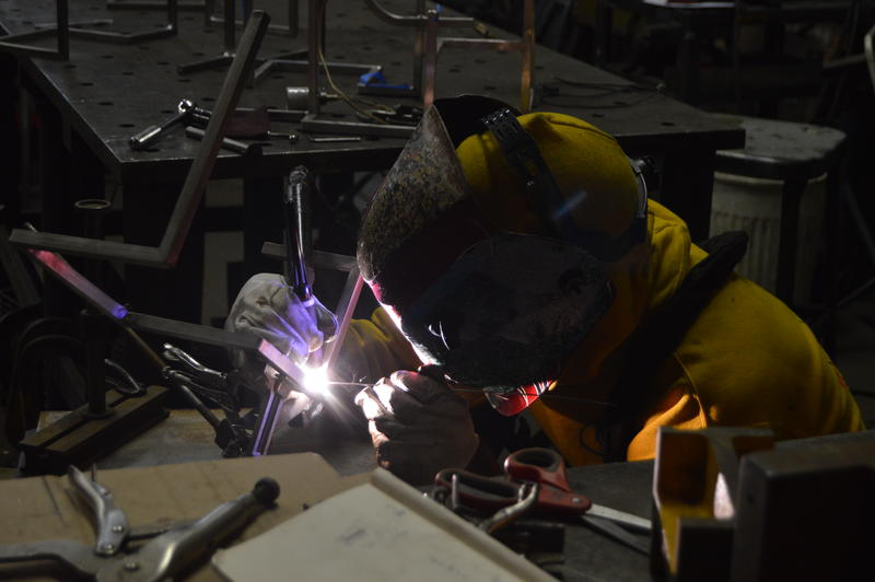 One of the Incite Design team members TIG welding part of a complex lighting structure.
