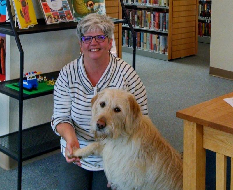 Zoe Redbird Radzibon listens to stories at the Presque District Library. She's pictured here with her owner, Kathy Radzibon, who manages the library's Onaway Branch.