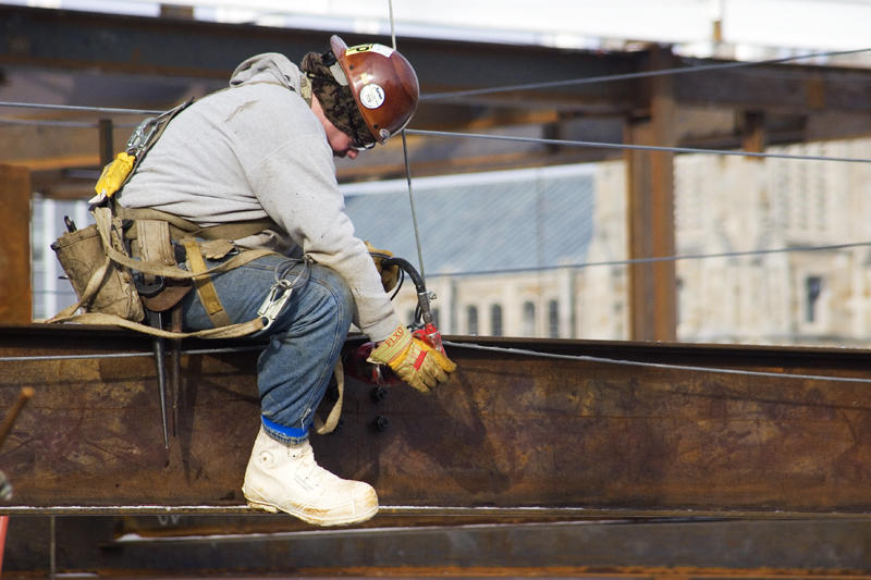 A steelworker straddling a beam