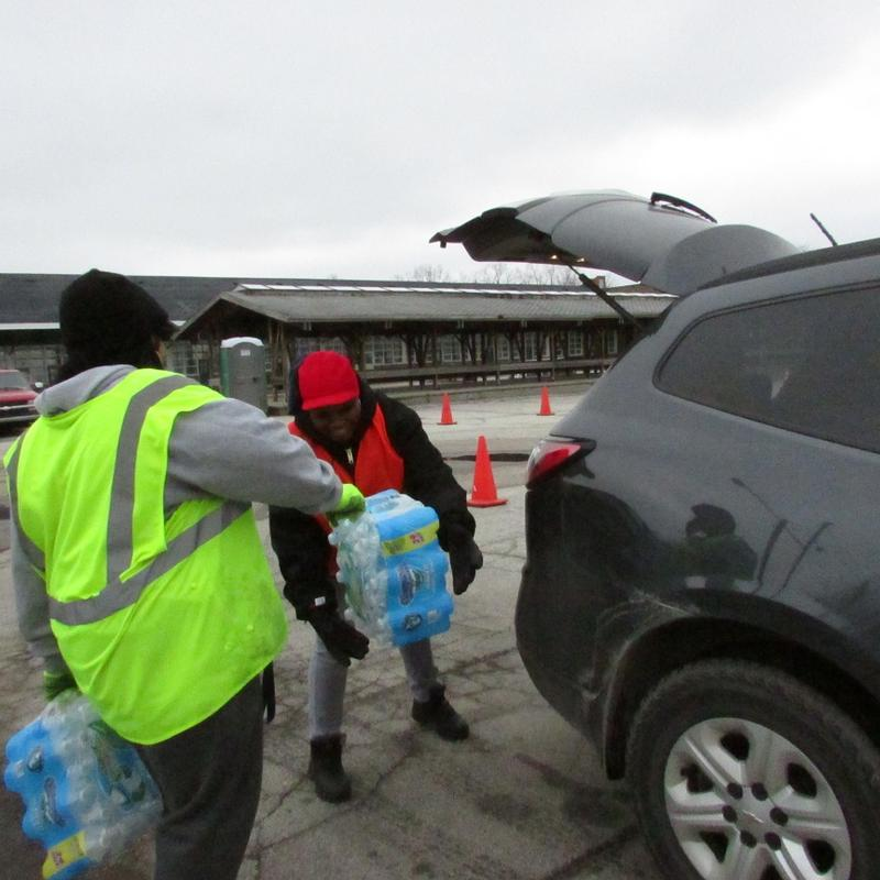 People loading cases of bottled water into an SUV