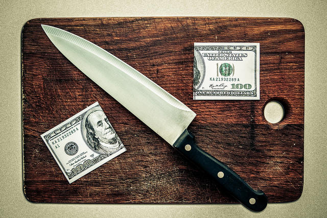A hundred dollar bill cut in half with a knife on a cutting board.