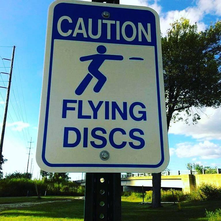 "A street sign that says, ""Caution, Flying Discs."""