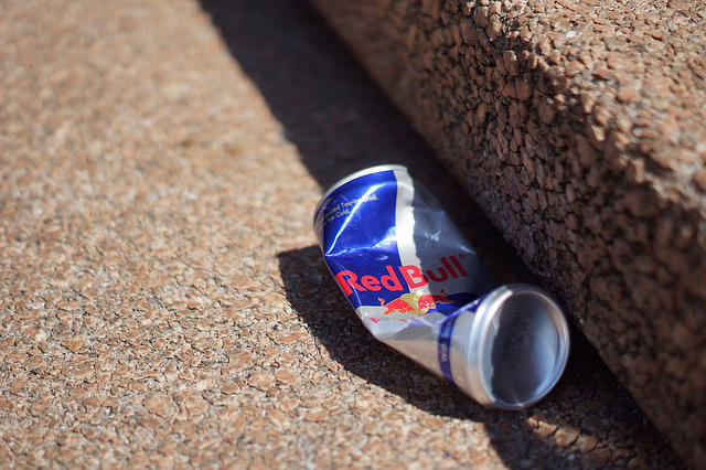 A crushed red bull can on the street