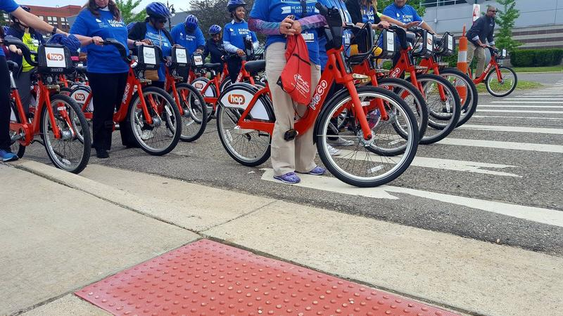 People getting on the MoGo bikes before a community ride out in Detroit