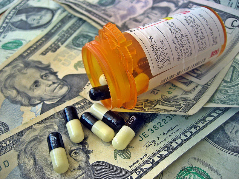 Money with bottle of pills