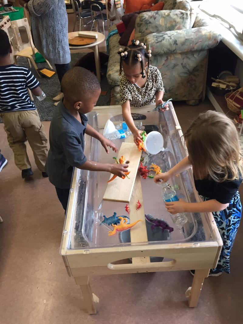 Children at Cummings Early Education Center play at a water table using bottled water