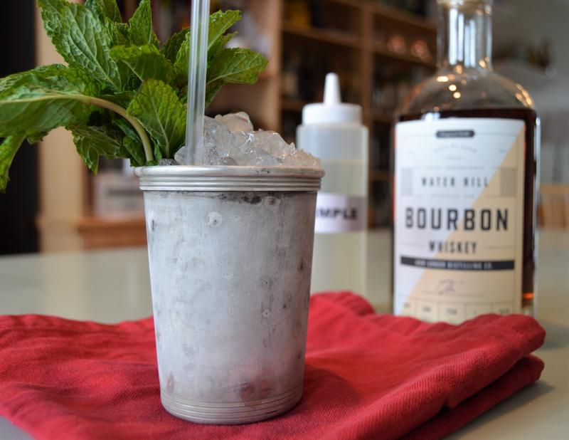 A mint julep sitting on a red napkin with a bottle of bourbon in the background
