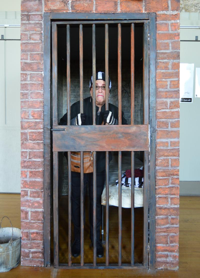 Judy Gail Krasnow stands inside one of the very small early prison cells.
