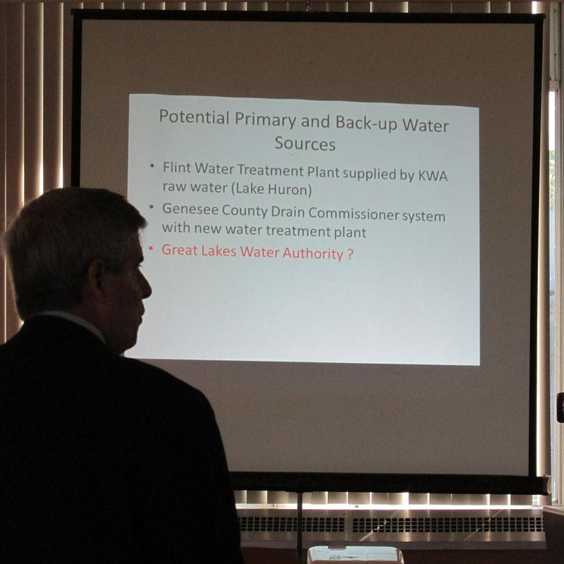 Consultant john Young stands in front of his Power Point presentation.