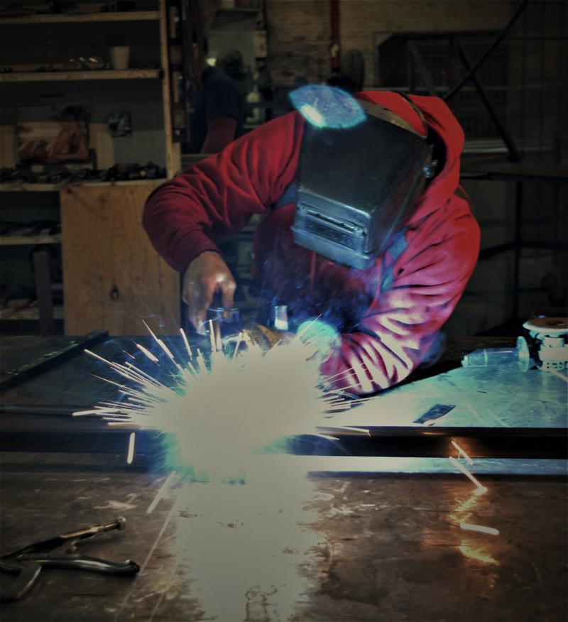 Welding an ornamental fence.