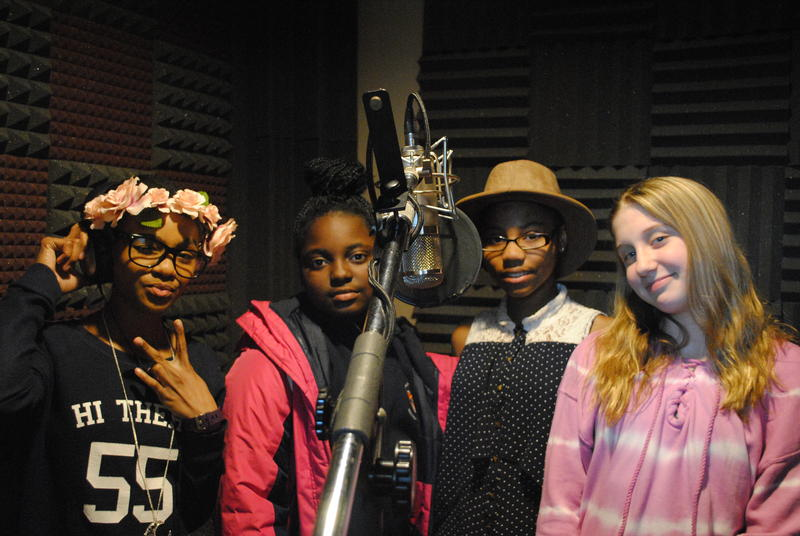 Four poets stand behind a mic to record their spoken-word album.