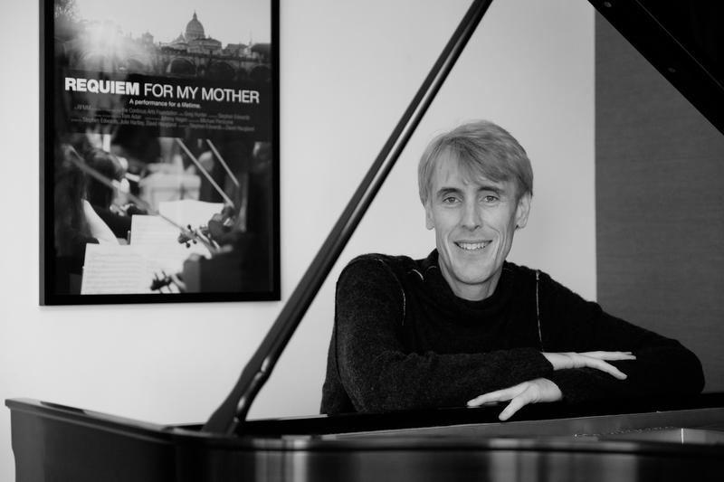 Stephen Edwards sits at a grand piano.