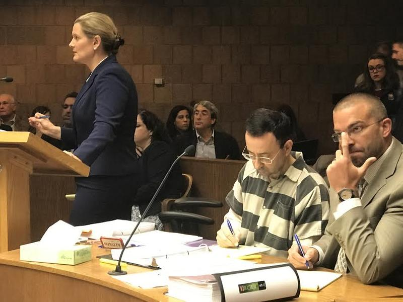 Assistant Attorney General Angela Povilaitis at a previous hearing. Larry Nassar sits next to one of his defense attorneys, Matt Newburg.