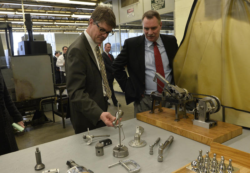 State Rep. Joe Haveman and Andy Ribbens, President of Premier Finishing in Grand Rapids, look over some of the products created by prisoners in the machines shop at the Richard Handlon Correctional Facility.