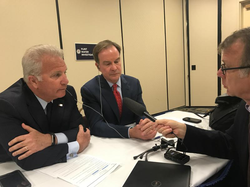 Michigan Attorney General Bill Schuette and Genesee County Prosecutor David Leyton sit across a table from reporter Rick Pluta.