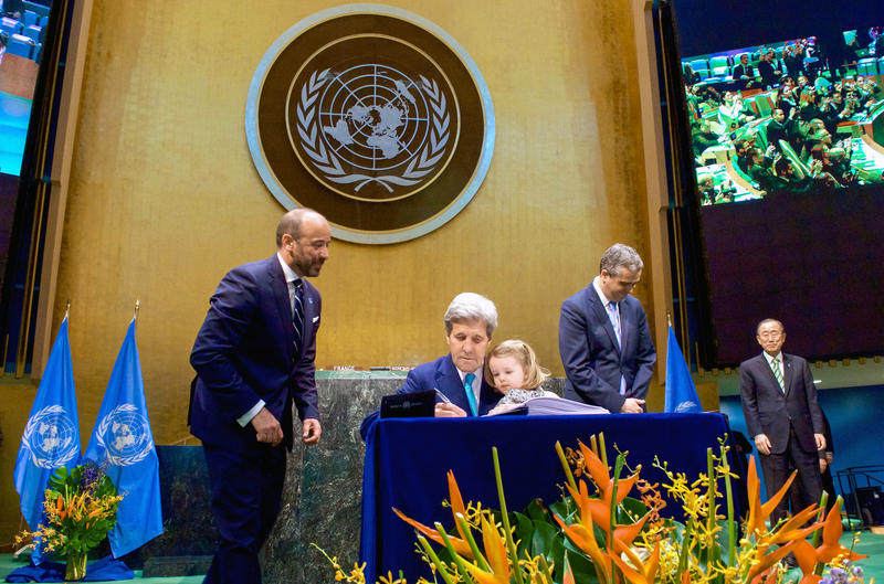 U.S. Secretary of State John Kerry, with his two-year-old granddaughter on his lap and United Nations Secretary-General Ban ki-Moon looking on on the [far right], signs the COP21 Climate Change Agreement on behalf of the United States on April 22, 2016