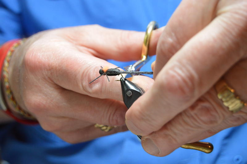 Close up of Dennis Potter's hands at work, trimming material from a fly.