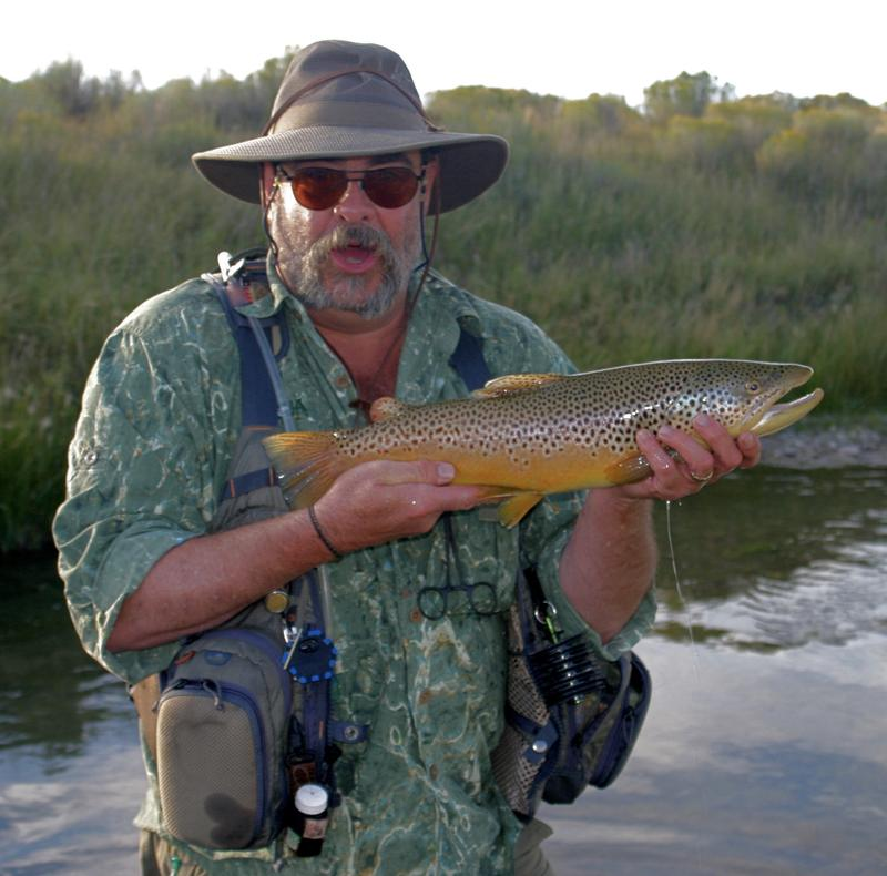 Dennis Potter holding up a fish, standing in the Au Sable River