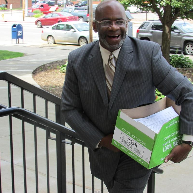 Recall organizer Arthur Woodson carries in a box with signed petitions to recall Flint Mayor Karen Weaver into the Genesee County clerk's office