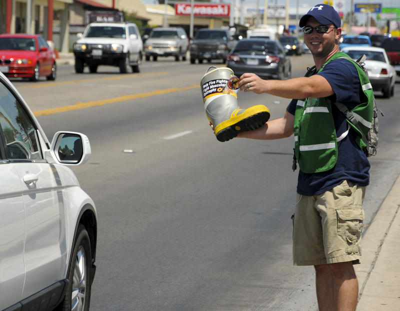 A man holding a firefighter boot and waving down cars for donations