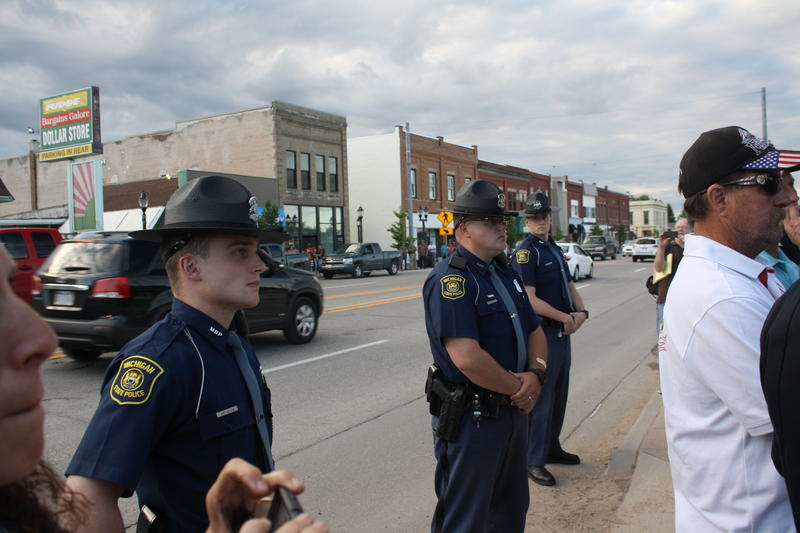 Three state troopers stand near the protest in Kalkaska.