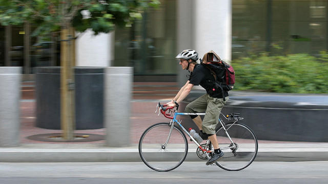 Person on bicycle riding in an urban area.